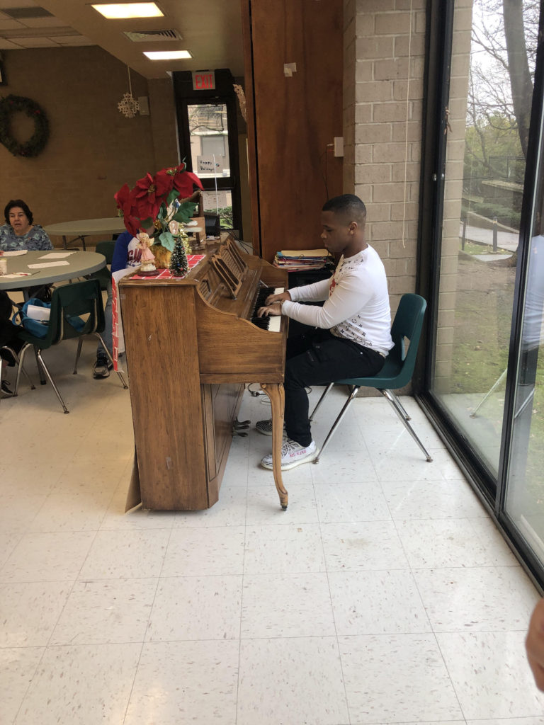 Student playing piano at the Shore Hill Senior Neighborhood Center
