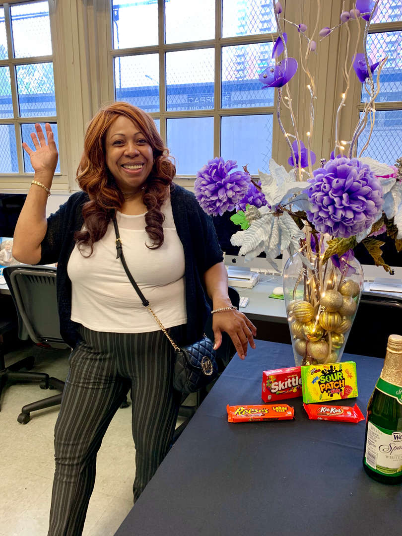 PTA member smiling and posing next to a table of candies and flowers