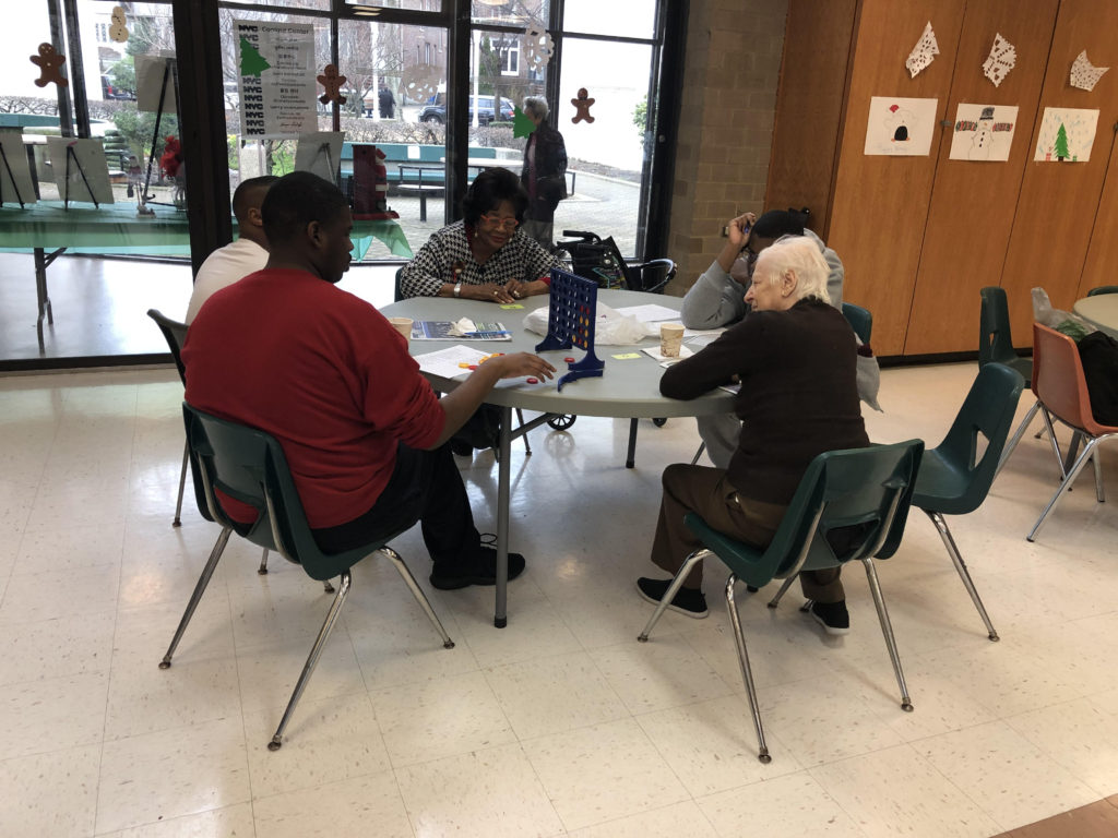 Students spending time with seniors at a table at the Shore Hill Senior Neighborhood Center