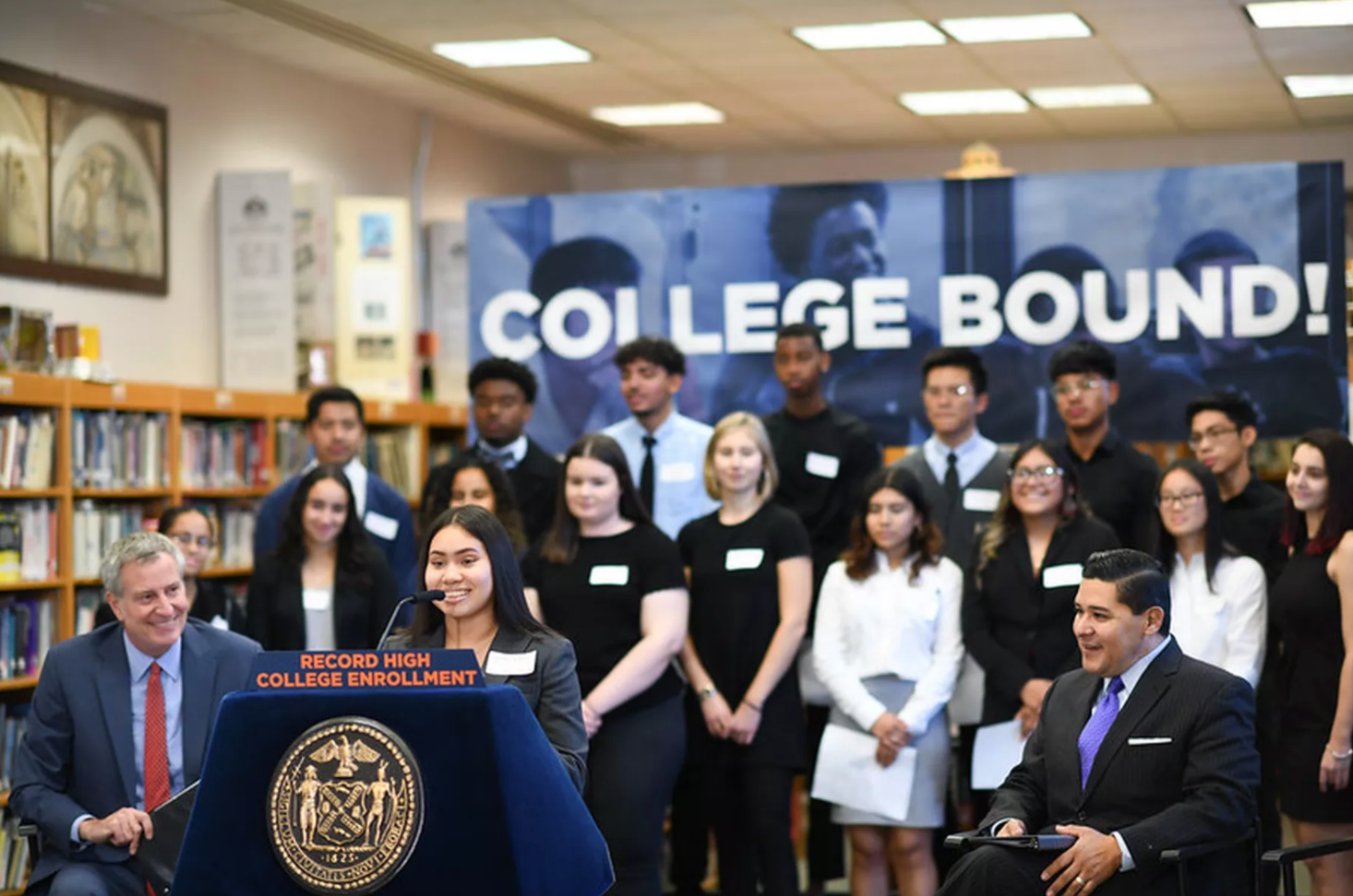 Mayor Bill de Blasio and Chancellor Richard Carranza listen to an alum  talk about her experience enrolling in college.