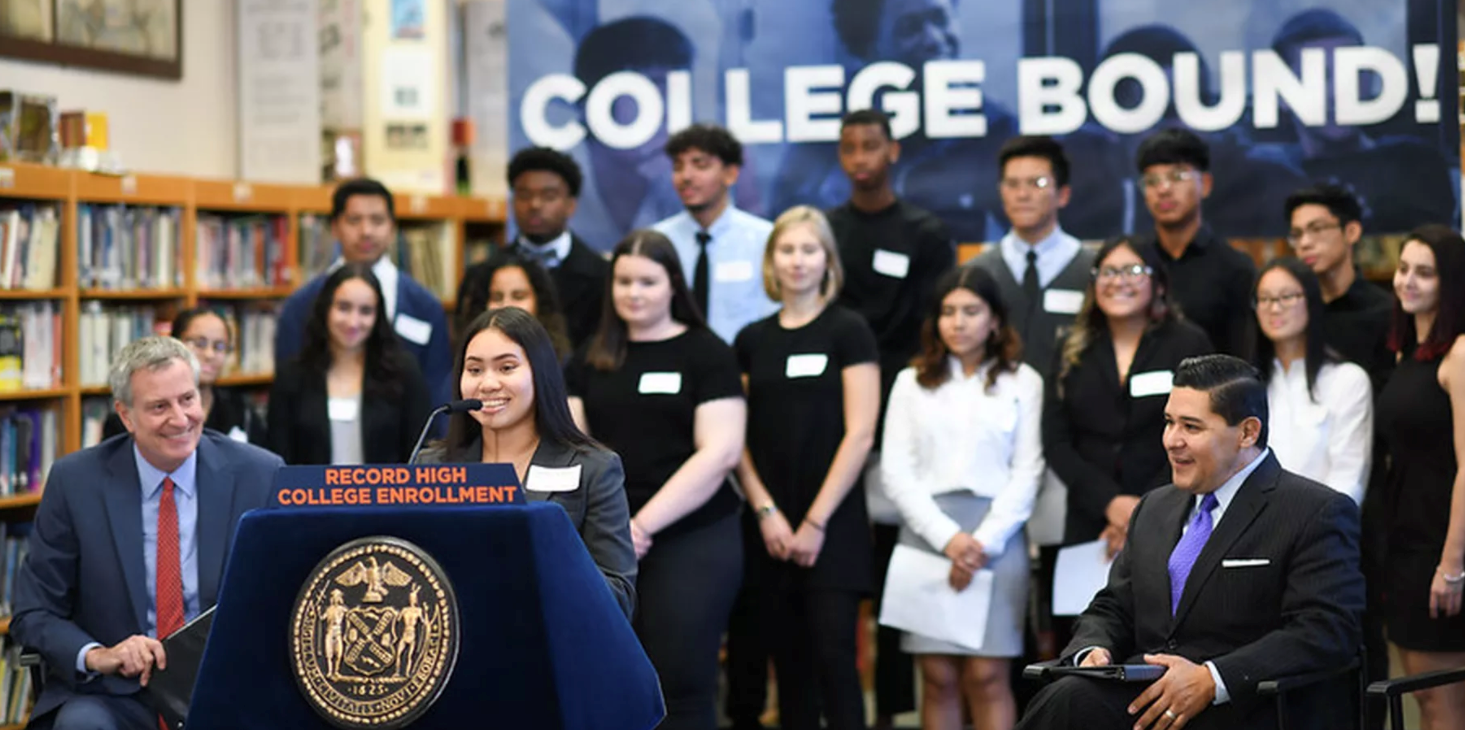 Mayor Bill de Blasio and Chancellor Richard Carranza listen to an alum talk about her experience enrolling in college
