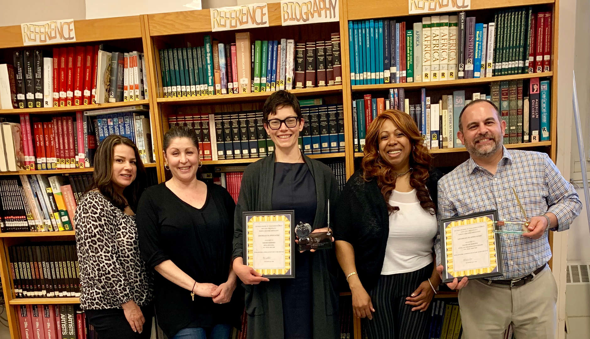 Five members of the PTA holding award plaques in the library