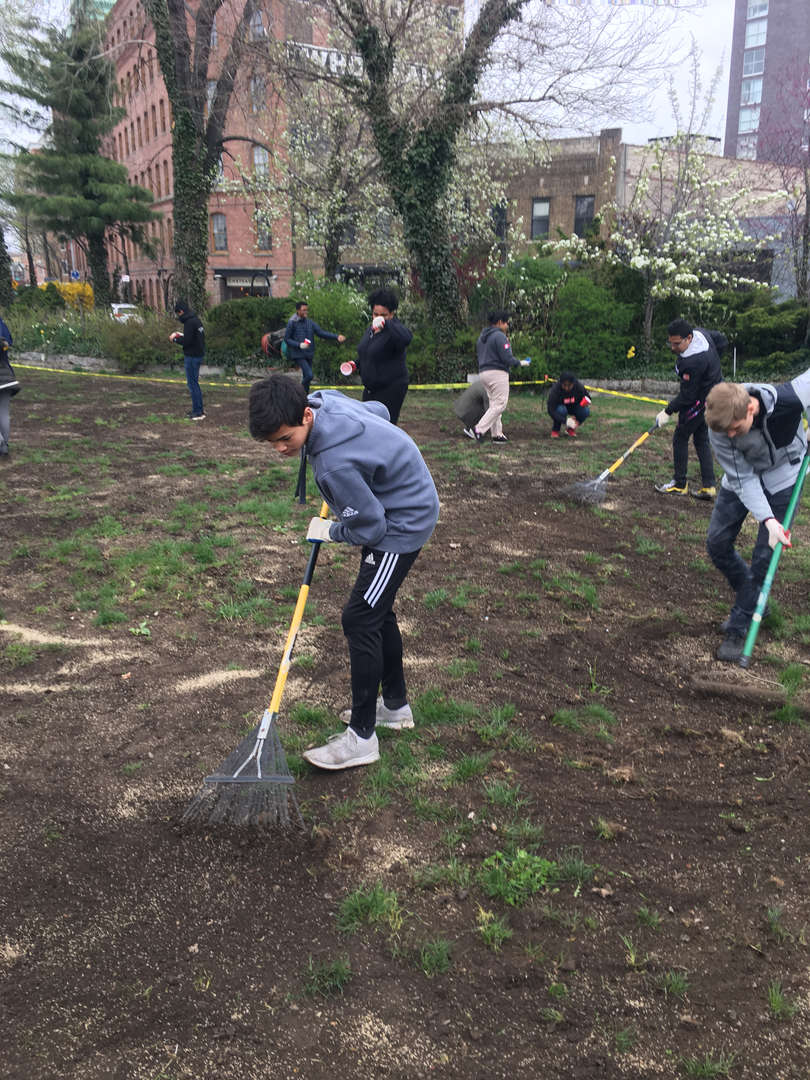 A group of students focused on raking the dirt ground