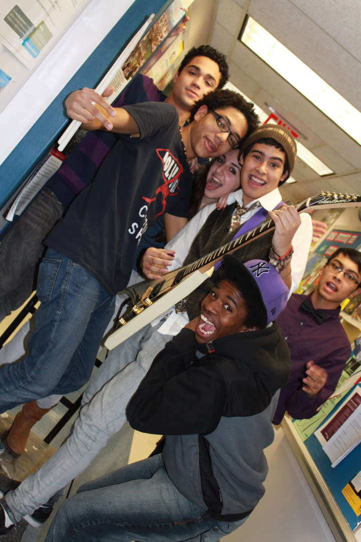 Students pose with joyous expressions around a student with a guitar