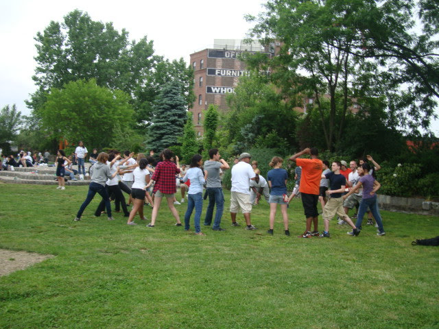 Students standing in a circle on the lawn dancing