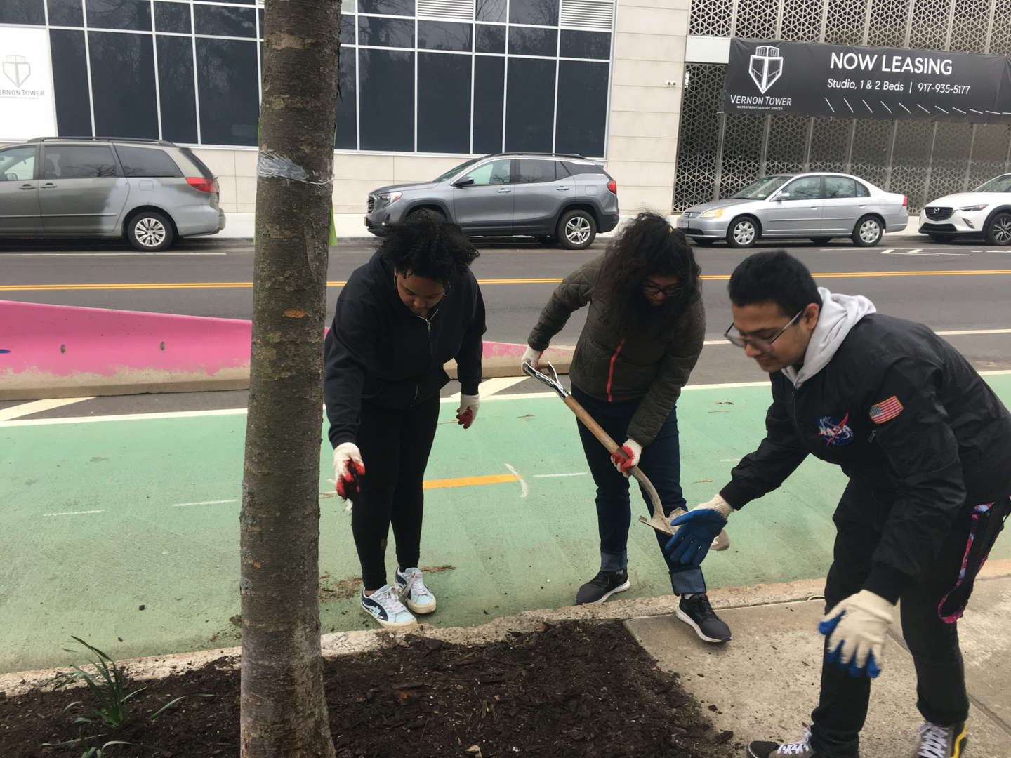 Student shovels dirt while two other students wearing gloves work beside them