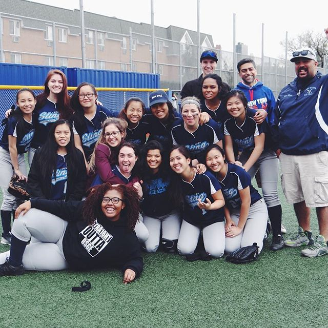 The girls' softball team posing on the field with their coach
