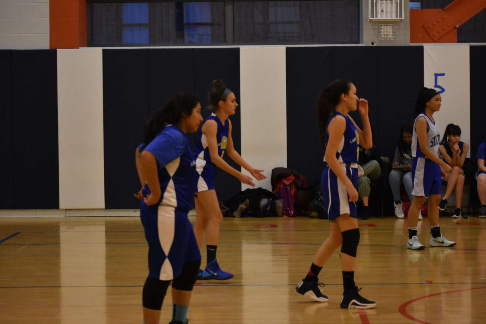 Members of the girls' basketball team waiting in anticipation on the court