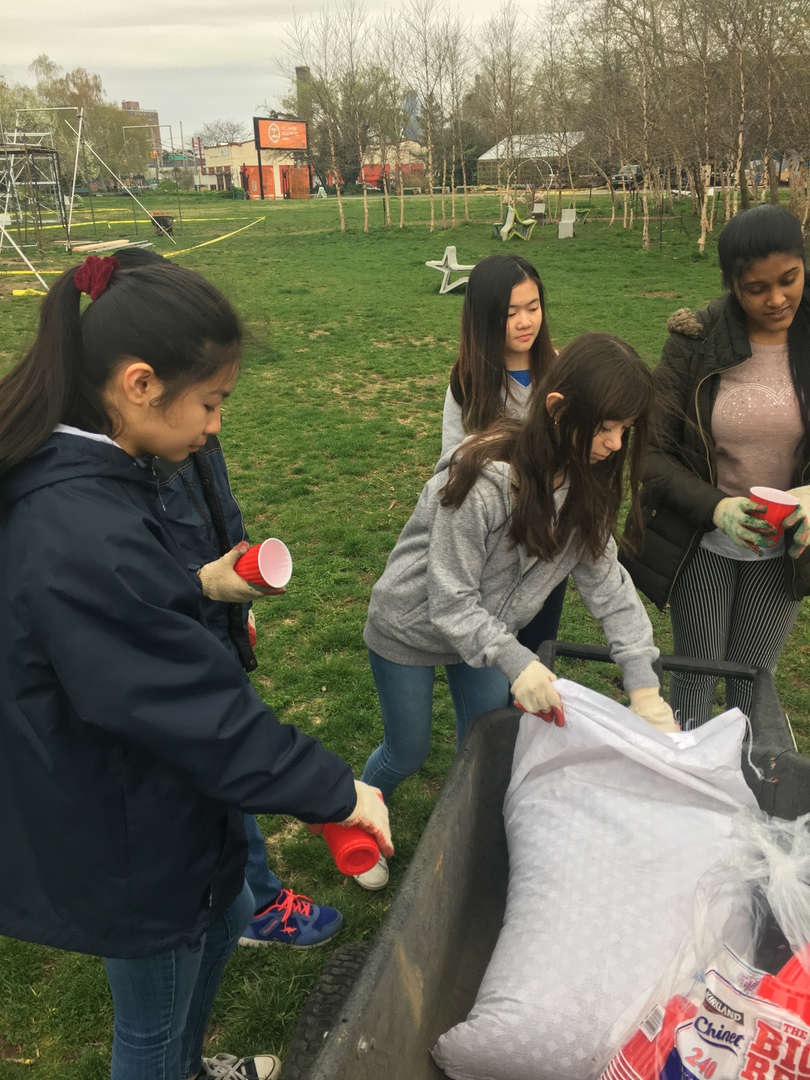 A student opens a garbage bag while others wait around her with their seed cups