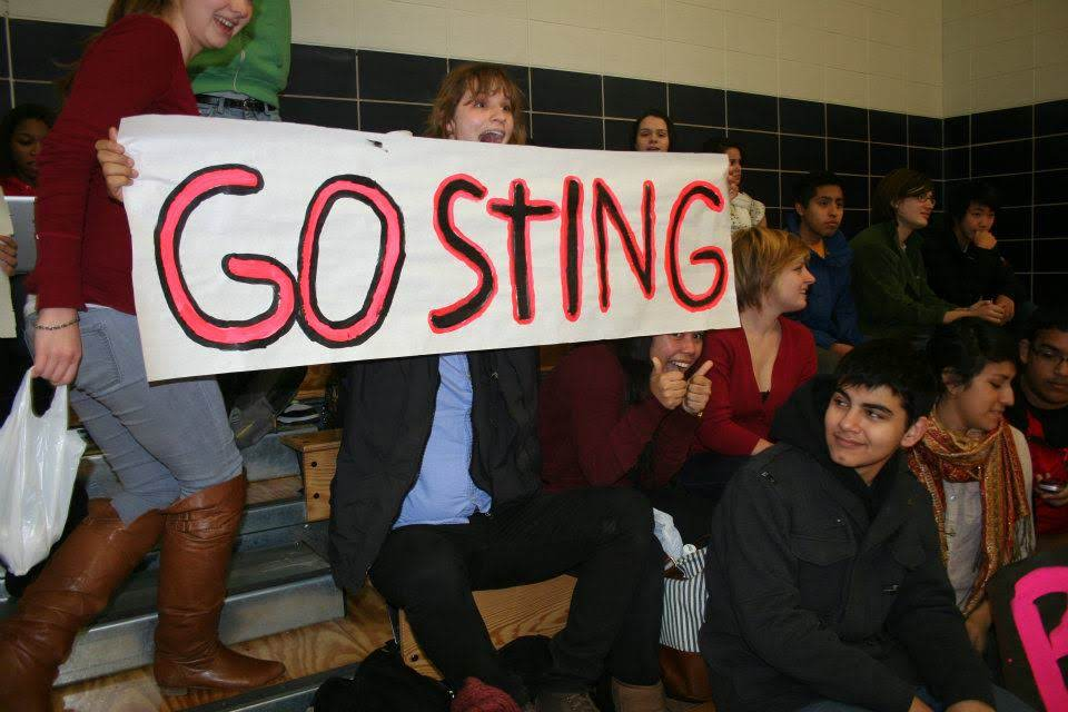 "Students holding a ""GOSTING"" sign in the bleachers"
