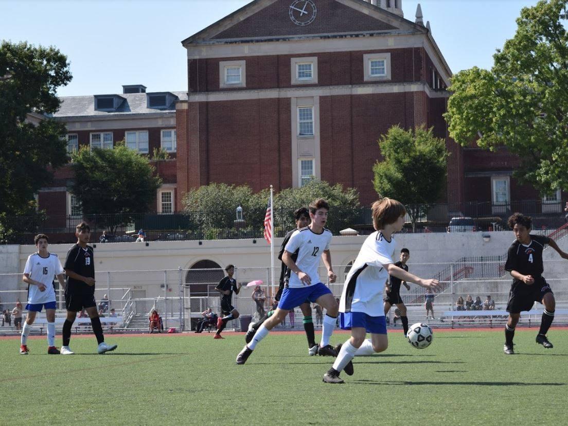 BSGE soccer player kicks the ball as the opposing team runs up