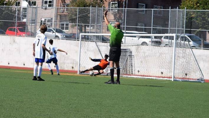 Referee with his hands up as the opposing team's goalie dives for the ball