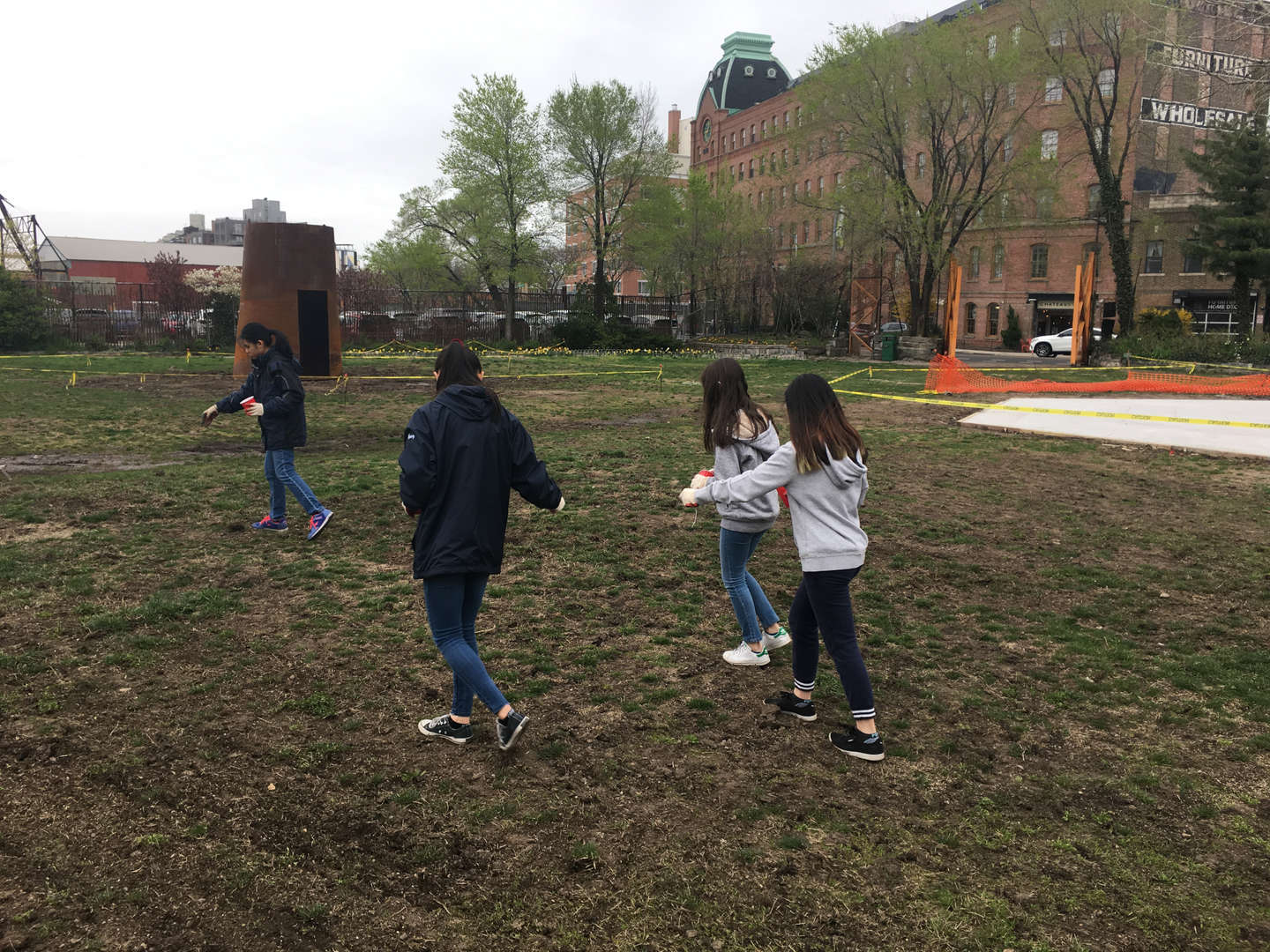 A group of four students seed the lawn