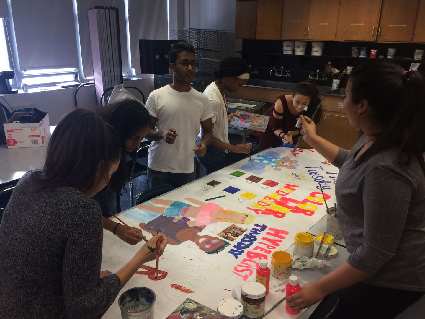 Students painting a sign together
