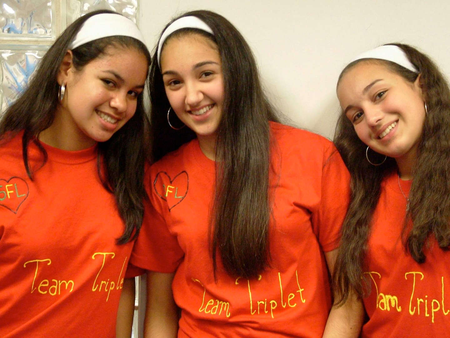 "Three girls wearing matching headbands and ""Team Triplet"" t-shirts"