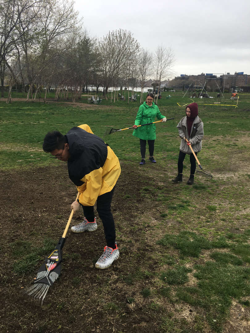 Three students holding rakes work on clearing the lawn