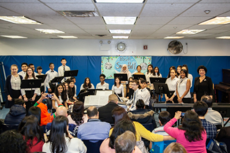 Students and music teacher smile toward the audience who are taking pictures