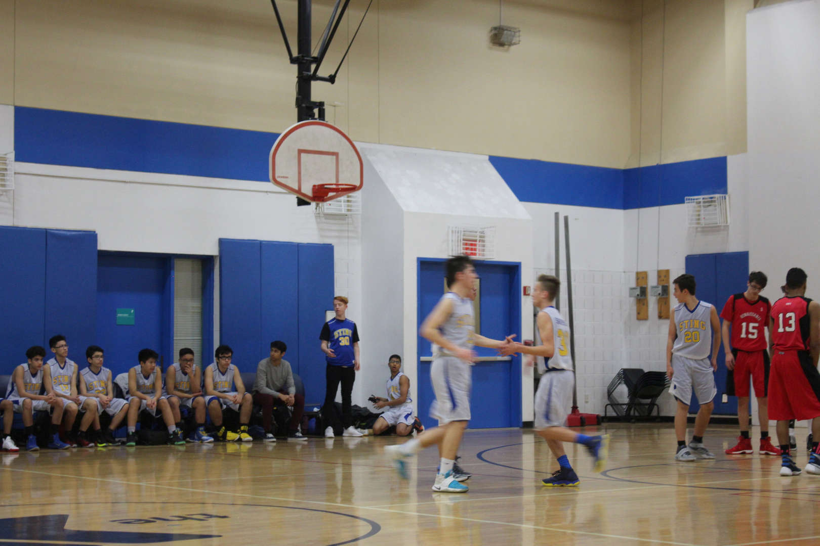 BSGE basketball players on the court while others watch from the sidelines