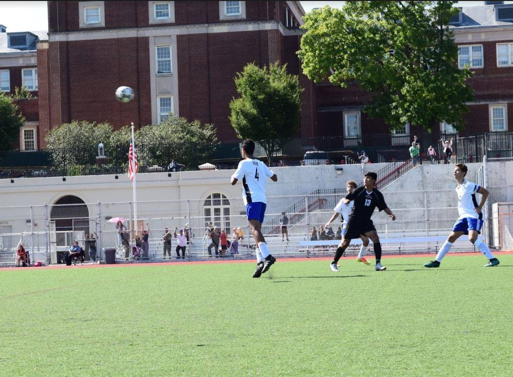 A soccer ball arching in midair toward a BSGE soccer player on the field