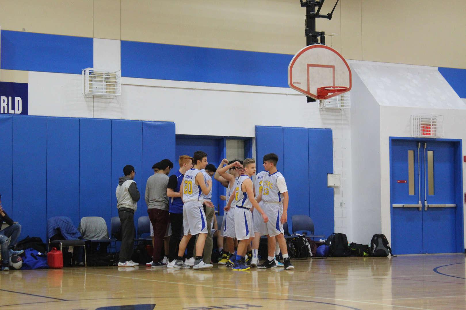 BSGE basketball team huddles on the sidelines