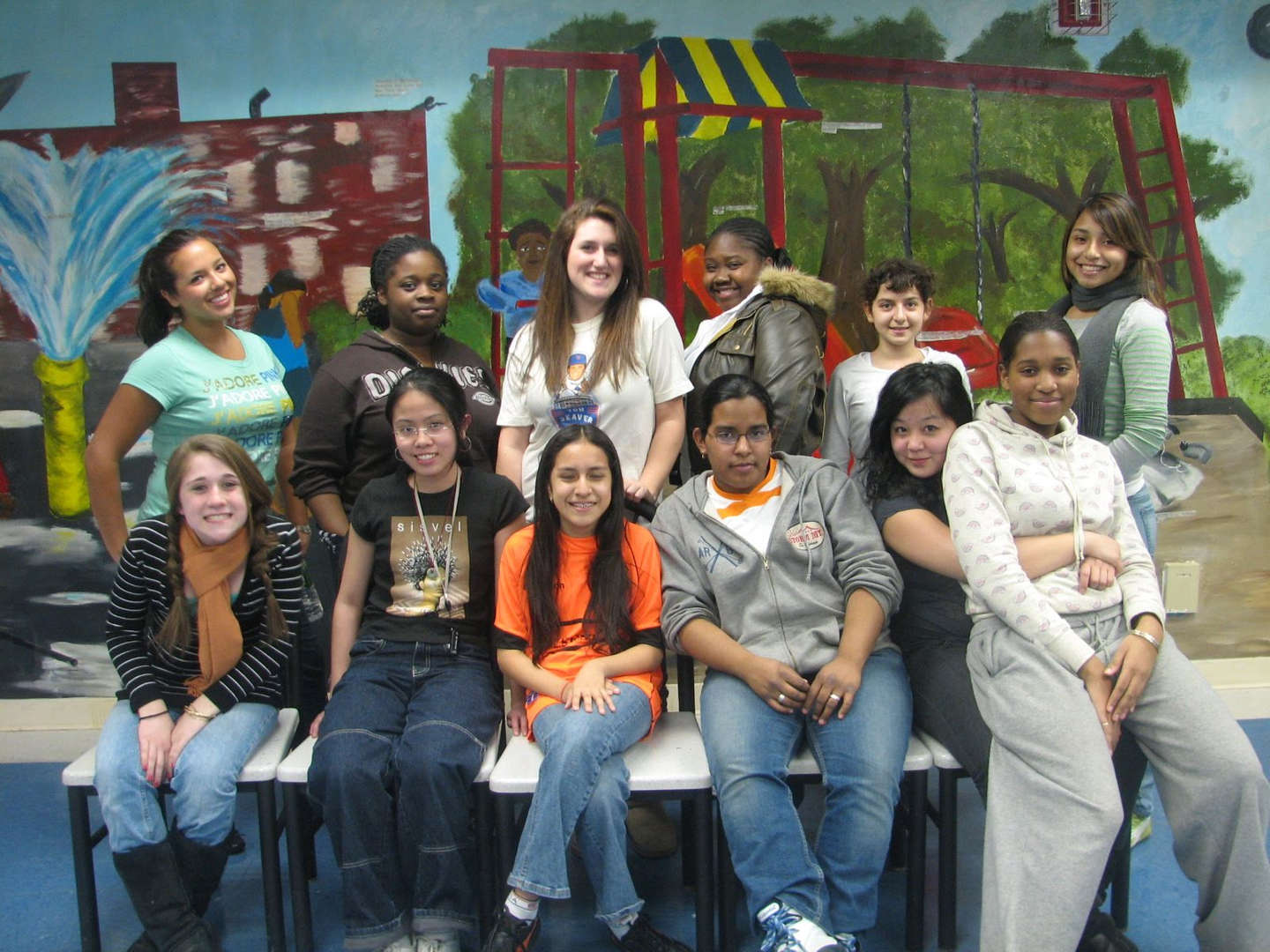A group of students in front of a colorful set backdrop