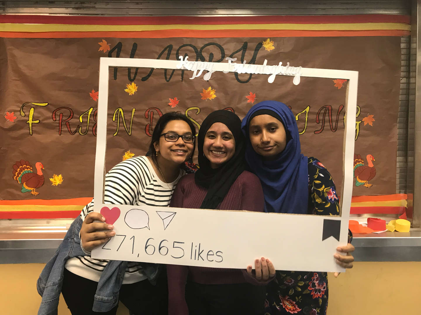 Students posing in a social media frame prop