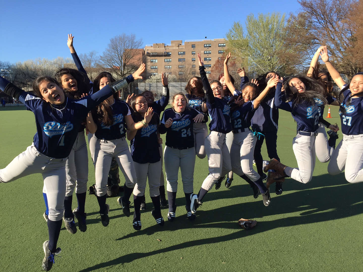 The girls' softball team jumping together