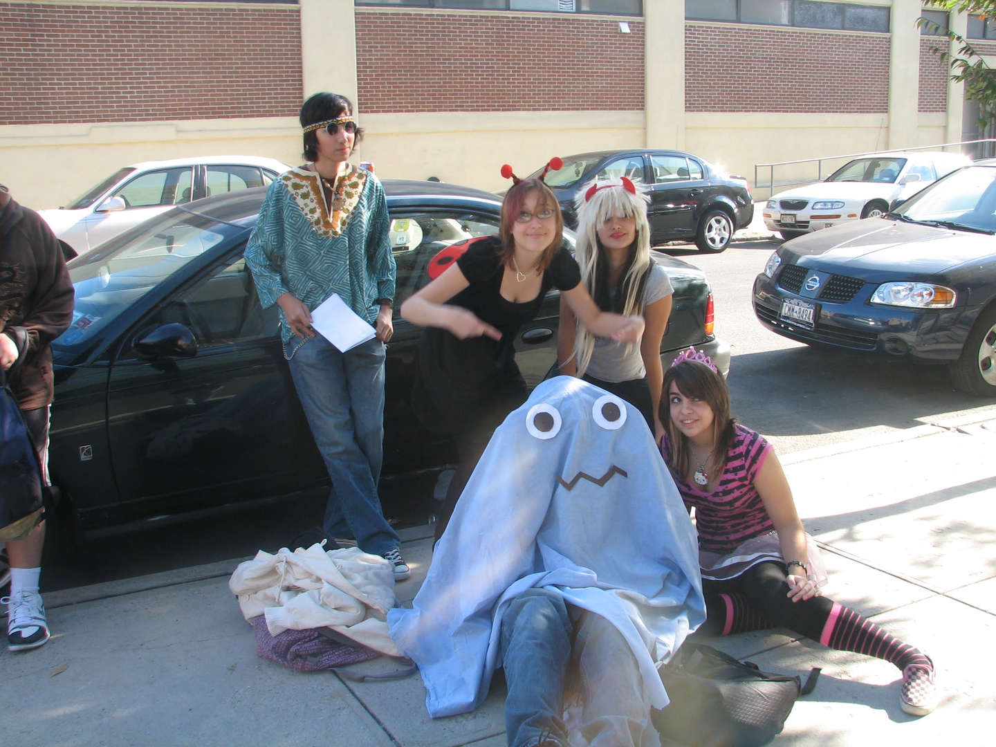 A group of students with various costumes sitting on the ground and leaning against a car