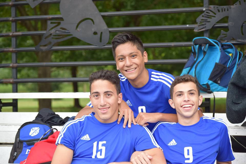 Three BSGE soccer players on the bleachers