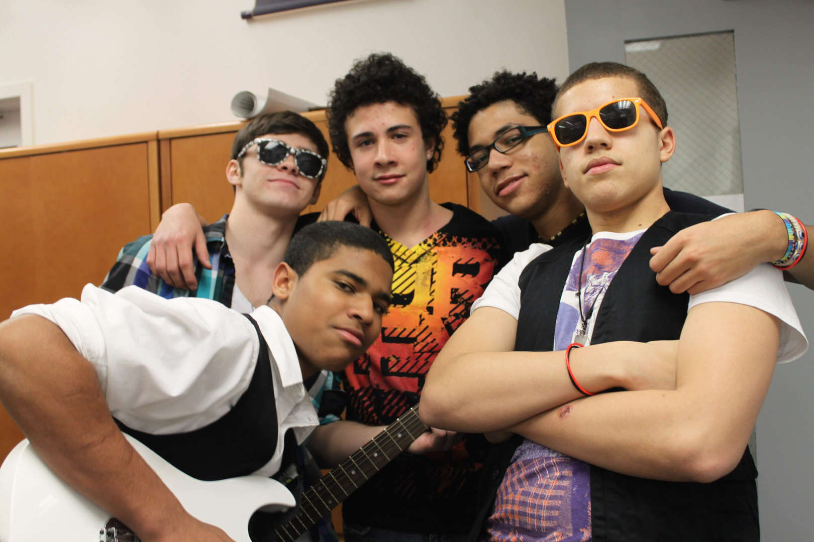 A group of students in the hall, two wearing sunglasses and one holding a guitar