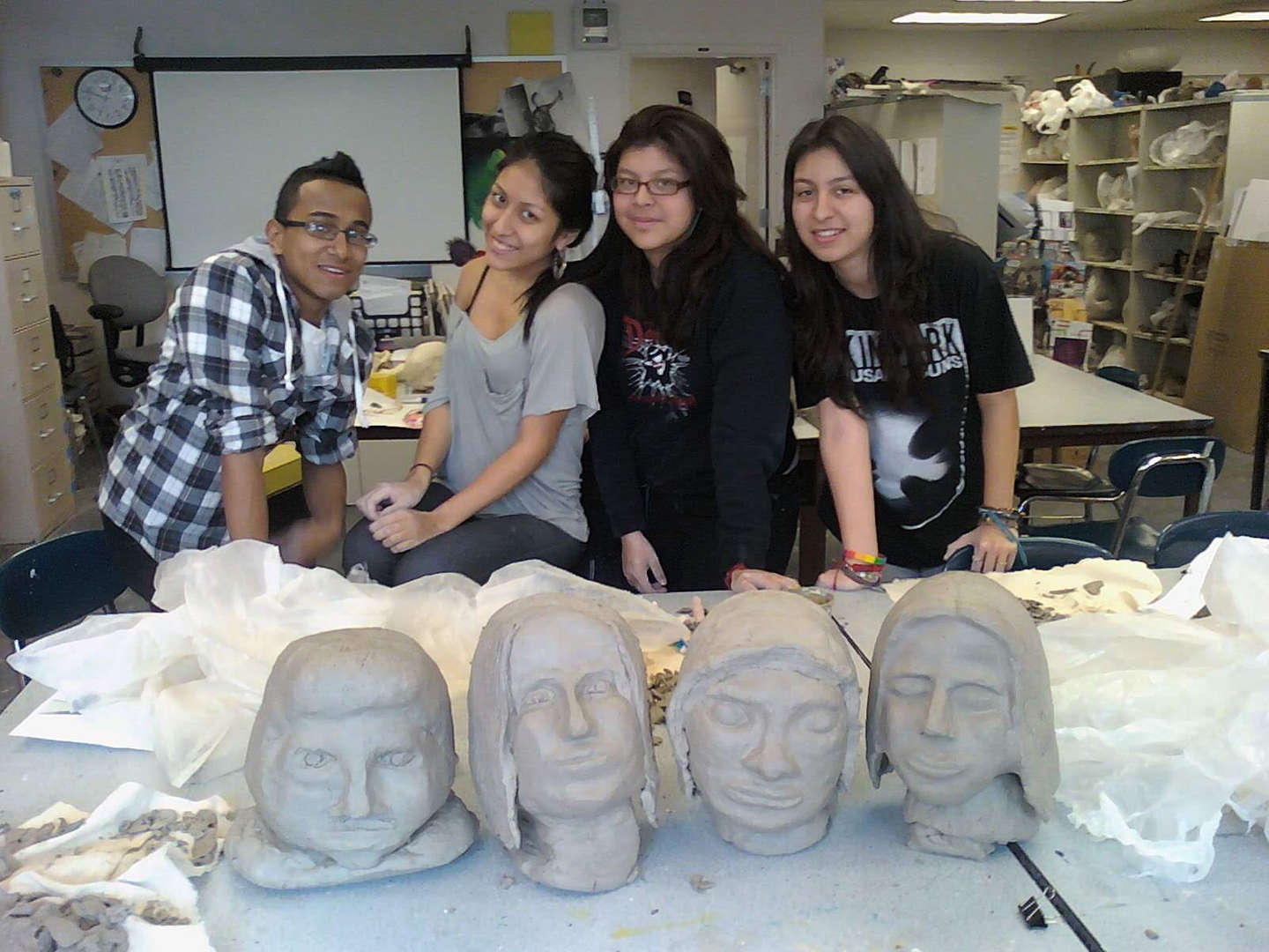A group of students standing behind their clay busts