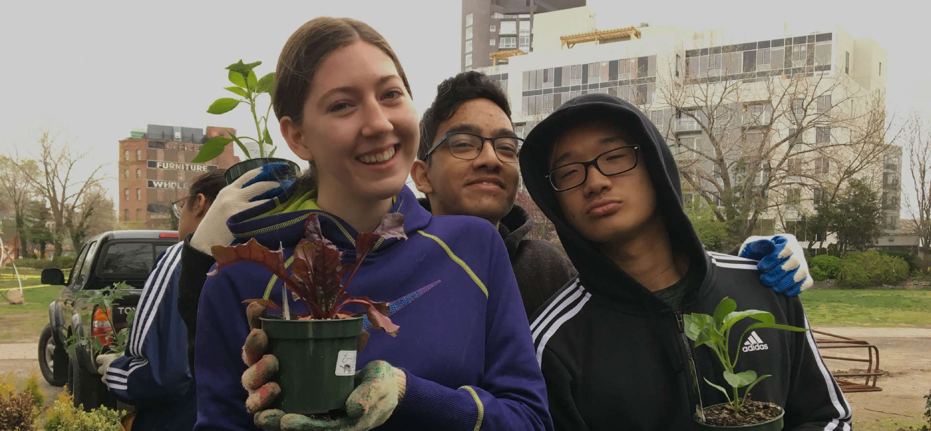 Three students holding plants
