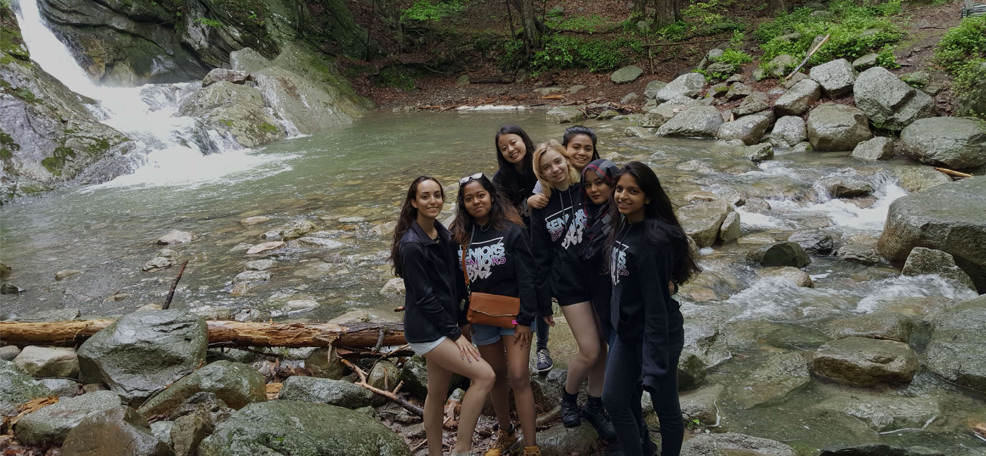 A group of students standing on rocks in front of a lake