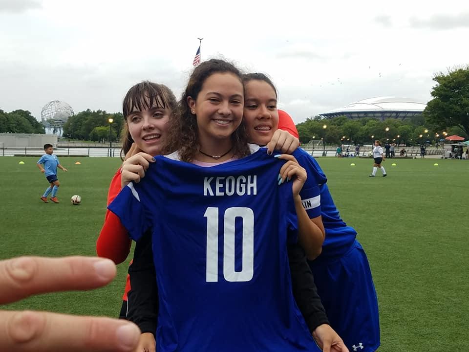 Soccer player holding up a Keogh jersey with her teammates
