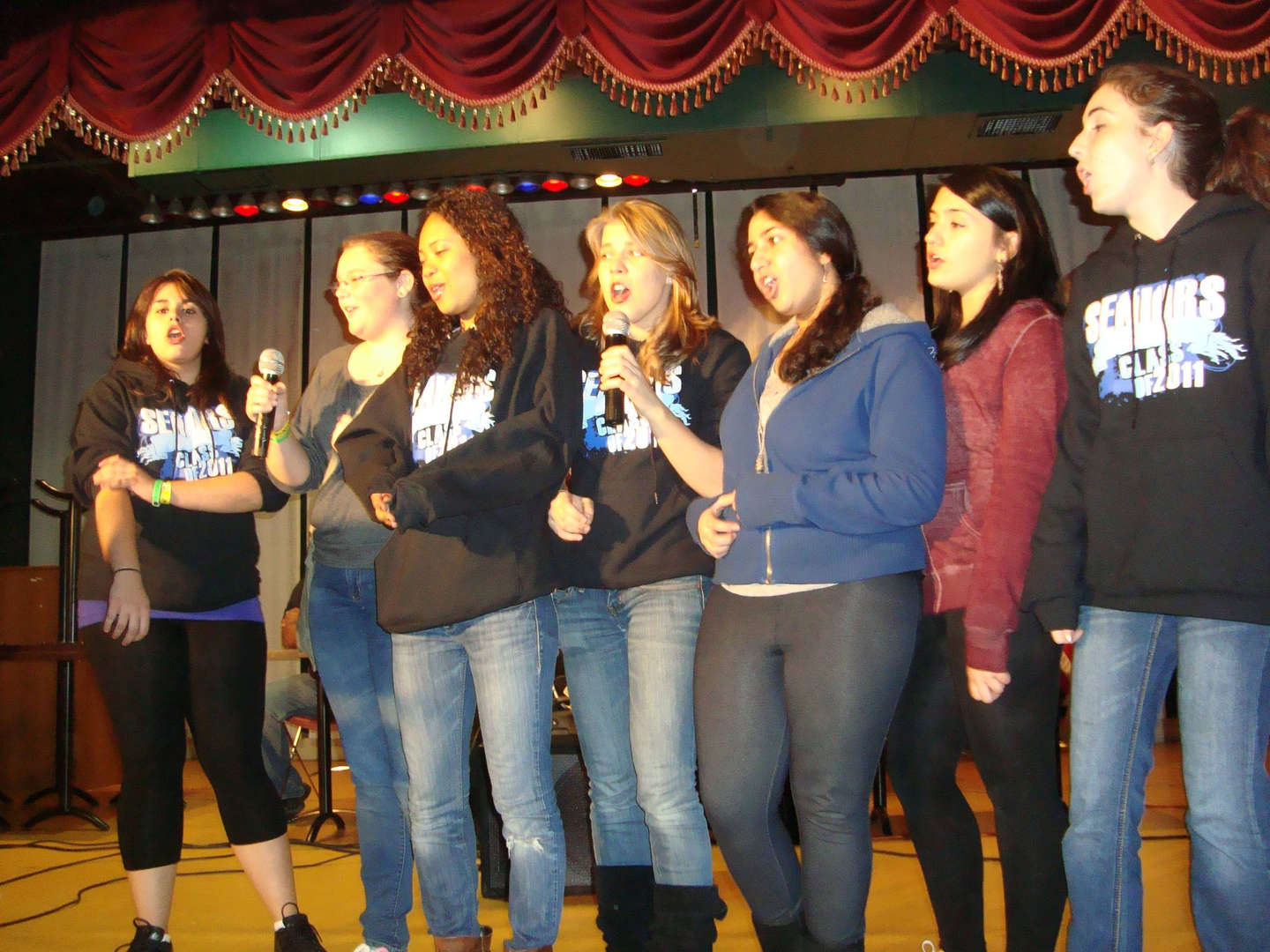 A group of students sing with microphones in their hands