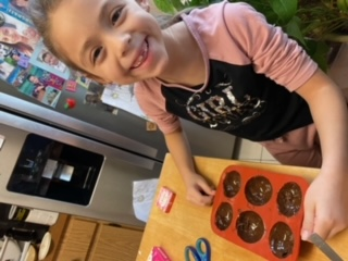 Kayla is putting the chocolate in the hot cocoa bomb mold.