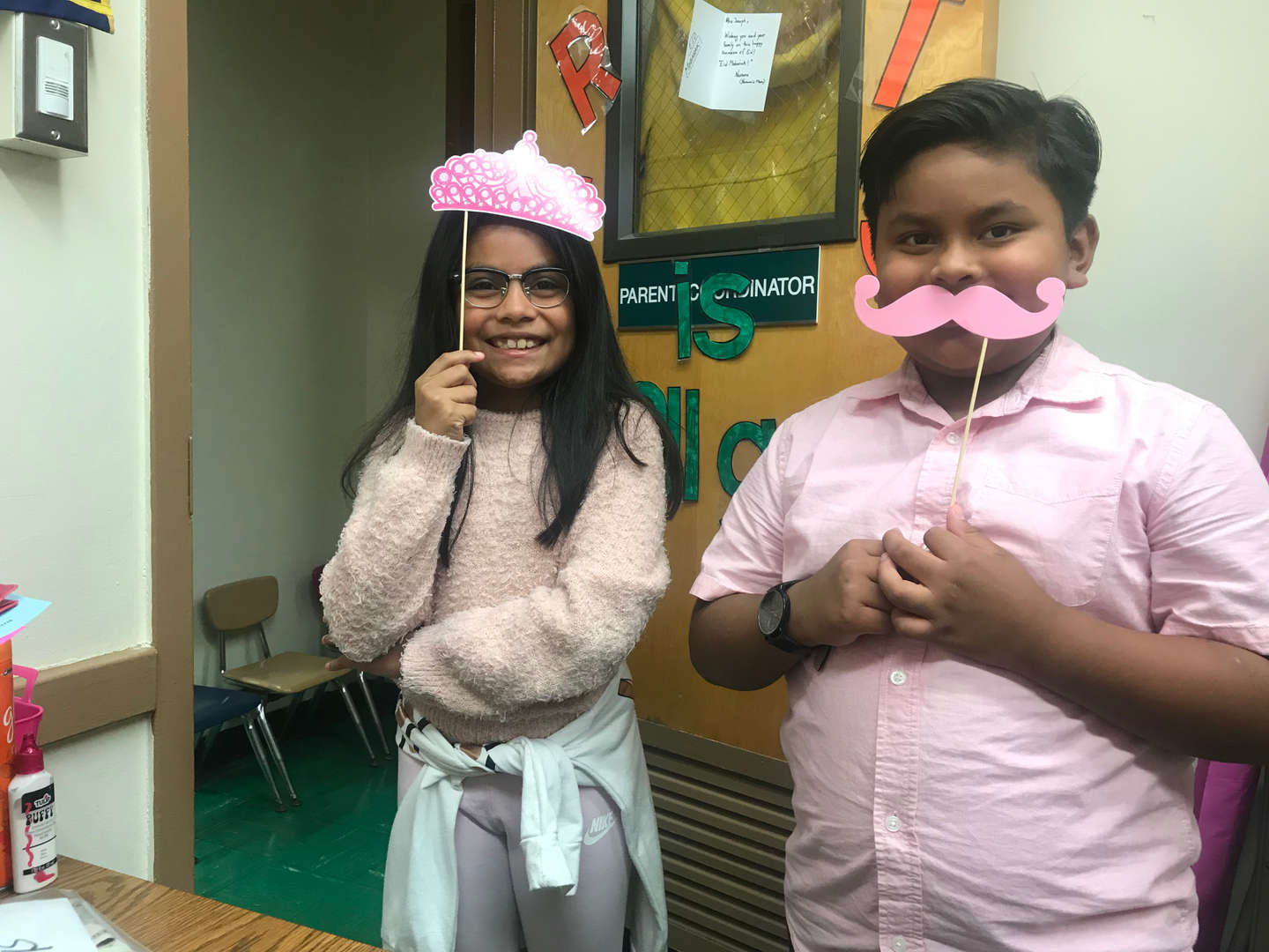 Two students dressed in pink with paper photo props