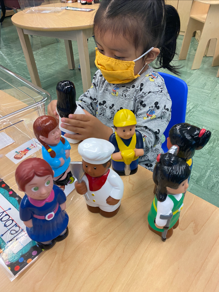 Student in mask playing with toys