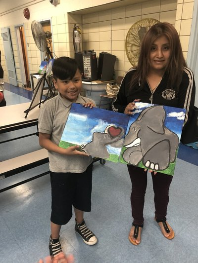 Boy and woman with paintings of two elephants with their tusks touching