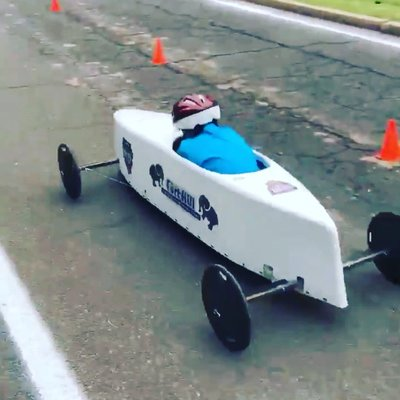 Student in a soap box derby car