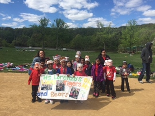 Teachers and students on a field with a sign for field day