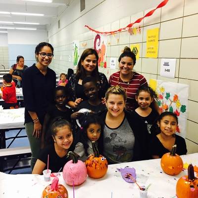 A group of teachers and students with their painted pumpkin