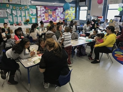 Moms and kindergarten students sitting together in the classroom
