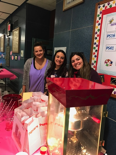 Three teachers smiling at the popcorn making table