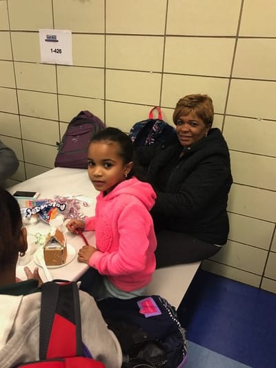 Student and parent with her gingerbread house