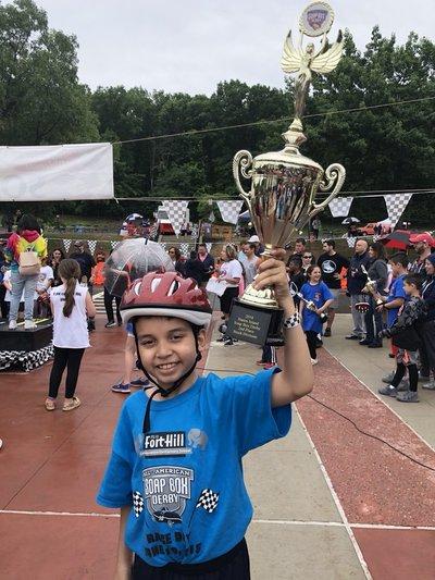 Boy holding soap box derby trophy