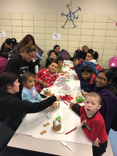 Students building gingerbread houses with teachers