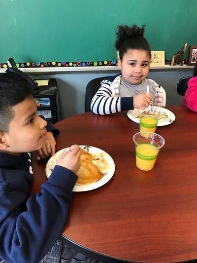 Two students enjoying a breakfast meal