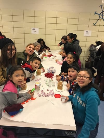 Students building gingerbread houses together
