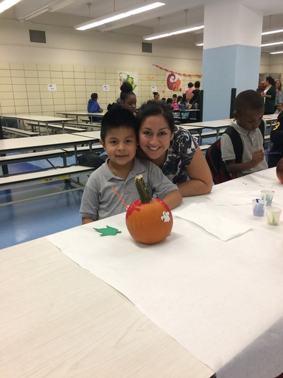 Student and teacher smiling with his pumpkin